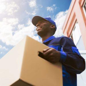 homme transportant un carton avec un sourire